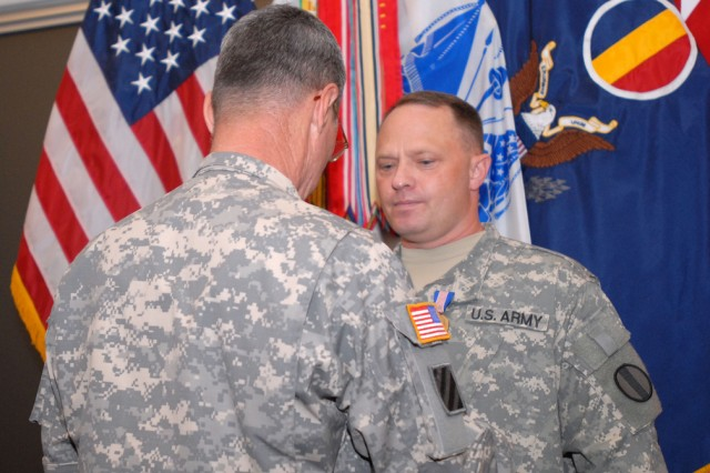Lt. Gen. John Sterling awards Chief Warrant Officer Clifford Bauman the Soldier's Medal at Fort Monroe, Va., July 23. Bauman was awarded the medal for his selfless service which saved three lives in October.