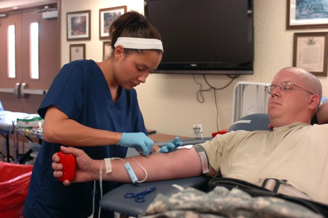 Christina Alandzes, a phlebotomist with the Southwestern Oklahoma Blood Institute, collects a blood donation from Sgt. Jeffery Jadwisiak, a regular blood donor with Headquarters and Headquarters Battery, 2nd Battalion, 4th Field Artillery.