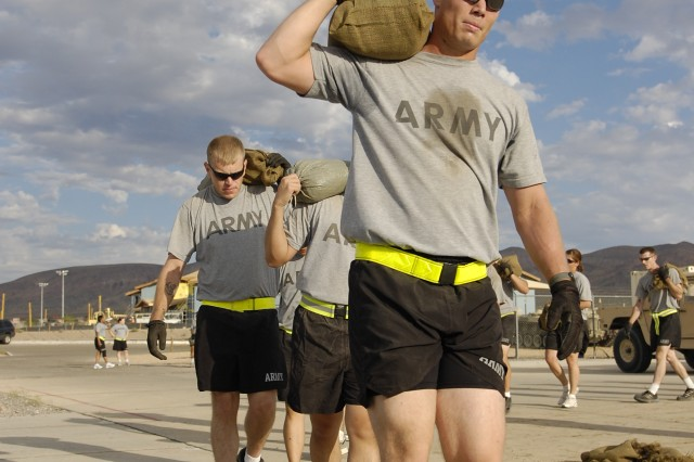 Soldiers from Regimental Headquarters and Headquarters Troop, 11th Armored Cavalry Regiment, lift sandbags as part of Motorpool Mondays, a physical training session conducted at the RHHT's motorpool at Fort Irwin, Calif., July 26. (Photo by Spc. Zachary A. Gardner, 11th ACR PAO)