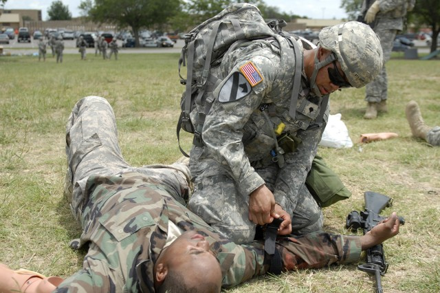 "FORT HOOD, Texas - Spc. Christian Balas, from San Jose, Calif., places his knee above a tourniquet on the right arm of a ""wounded"" Soldier during Expert Field Medical Badge training, here, July 21. Balas serves as combat medic with Headquarters and Headquarters Troop, 6th Squadron, 9th Cavalry Regiment, 3rd Brigade Combat Team, 1st Cavalry Division."