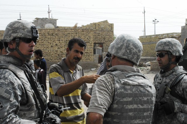 An Iraqi man speaks to Sgt. 1st Class Kenneth Sergeant, project purchasing officer  with Headquarters and Headquarters Troop, 4th Squadron, 10th Cavalry Regiment, 3rd Brigade Combat Team, 4th Infantry Division, about the electrical problems Dhi Qar has experienced recently, July 15.