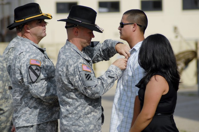 FORT HOOD, Texas - Col. Douglas Crissman, the commander of 3rd Brigade Combat Team, 1st Cavalry Division, pins a Purple Heart Medal on former Sgt. Juan Castro, here, July 26.  Castro sustained injuries as part of a combat logistical convoy in Diyala province in 2007 where he served as a mechanic with D Troop, 6th Squadron, 9th Cavalry Regiment.