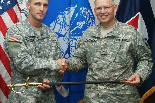 Spc. Alex Perenishko, Surface Deployment and Distribution Command is presented with a sword and other gifs by  Brig. Gen. Steven Feldmann, ASC deputy commanding general for operations, after winning Army Materiel Command's Soldier of the Year. He will represent Army Materiel Command at a Department of the Army competition in October.