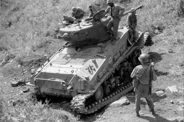 Men of the 2nd Platoon, Company B,10th Engineer Battalion, check a tank for booby-traps and the area for mines, Oct. 8, 1951.