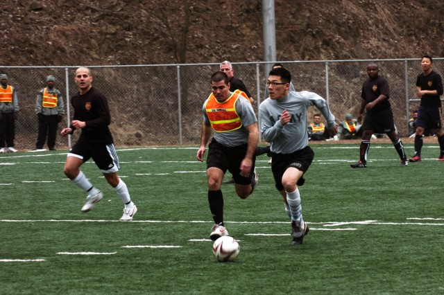 """""""Spartans"""" from the 1st Brigade Special Troops Battalion and """"Guns"""" from 1st Battalion, 15th Field Artillery Regiment, 1st Heavy Brigade Combat Team, race for a ball during a soccer match on Camp Hovey."""