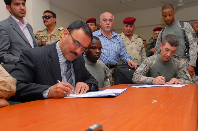 Lt. Col. Robert Ashe (center), commander of 2nd Battalion, 69th Armor Regiment, looks on as Sameer Alhaddad, the representative for receivership of the chief of staff of the Iraqi prime minister, and Capt. Michael Washburn, commander of Company A, 2nd Battalion, 69th Armor Regiment, sign documents officially transferring full ownership of Patrol Base Mahawil to the Iraqi Army in Babil Province, July 25.