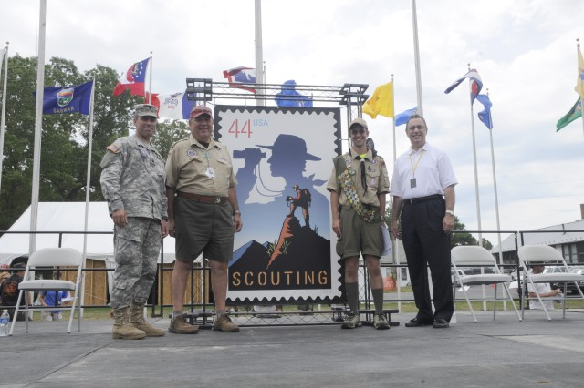 """FORT A.P. HILL, Va. – Guest speakers pose alongside a large-scale mock-up of the new 100th Anniversary Scouting stamp  at the U.S. Postal Service's commemorative centennial Scouting stamp """"first day of issue"""" ceremony at the Boy Scouts of America's 2010 National Scout Jamboree July 27. The stamp, titled """"Celebrate Scouting,"""" was designed by California-based illustrator Craig Frazier, and features a Scout atop a cliff gazing into the distance, superimposed over the silhouette of a Scout looking through binoculars. (U.S. Army photo/Sgt. Marie Adams)"""