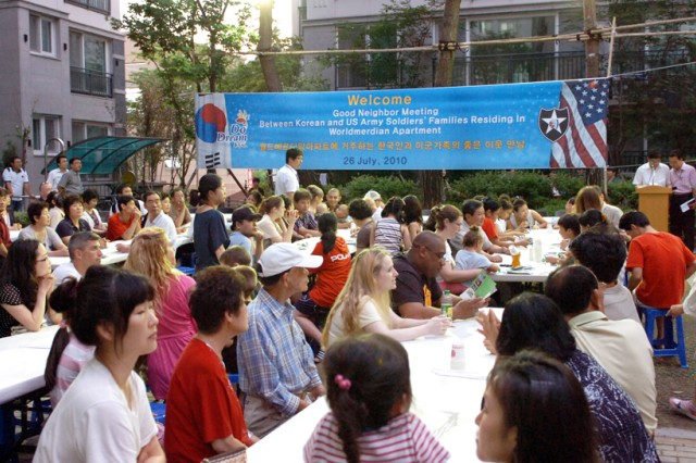 "Korean and American families living in the World Meridian Apartment complex in Dongducheon gather for a special ""good neighbor meeting"" called by Mayor Oh Sea-chang July 26."