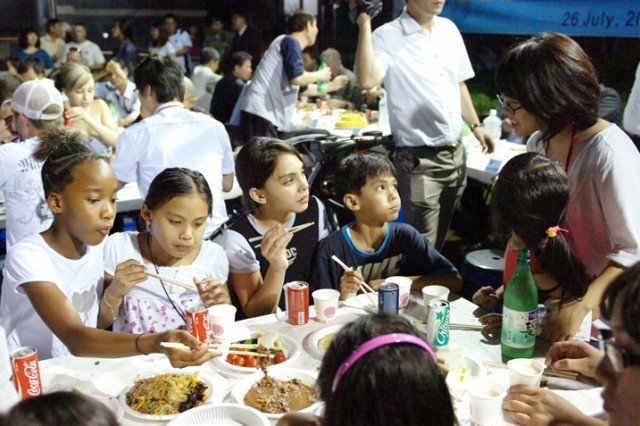 "Children of U.S. Army families living at the World Meridian Apartments enjoy the Korean food that was served during the special ""good neighbor meeting"" called by Dongducheon Mayor Oh Sea-chang at the complex July 26."