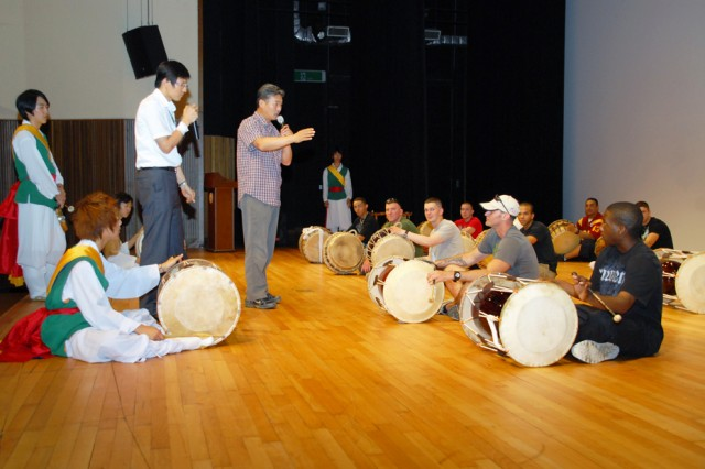DONGDUCHEON, South Korea - Casey Garrison Soldiers get a quick lesson in how to play traditional Korean farmer's music on the janggu (hourglass drum) and buk (barrel drum) from Kim Hung-rae, first leader of Dongducheon's Edam Pungmulnori group, during a stop at the Dongducheon Culture Center July 20. Thirty Soldiers participated in the free monthly half-day orientation tour of Dongducheon that visited a traditional market, Jajae Temple and the Freedom Protection Peace Museum before concluding with dinner at a Korean restaurant.