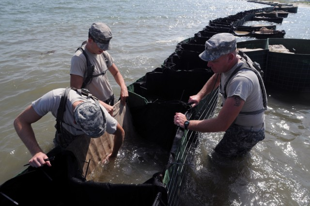Soldiers from the Alabama National Guard build and maintain miles of HESCO barriers to protect Dauphin Island, Ala., beaches from the BP oil spill on July 23, 2010. More than 1,600 National Guardmembers are supporting Operation Deepwater Horizon in four Gulf states.