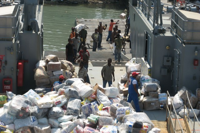 Haitians offload humanitarian disaster relief supplies from an Army LCU at the seaport of Port-au-Prince.