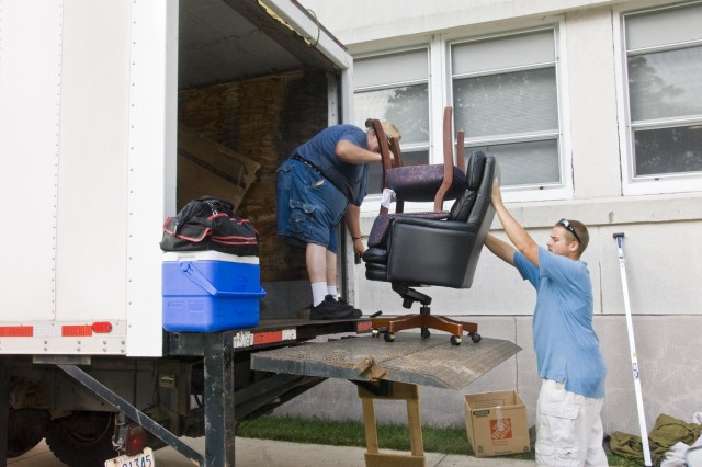Workers load trucks with furniture