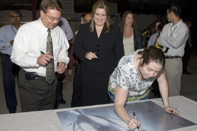 Employees with the Armament Research, Development and Engineering Center's Software Engineering Center, headquartered at Picatinny Arsenal, N.J., sign a poster during a celebration ceremony in July. The team recently became the first government organization in the U.S. to earn the Capability Maturity Model Integration (CMMI) Level 5 designation. This is the highest rating given to software engineering groups that meet CMMI's rigorous standards.