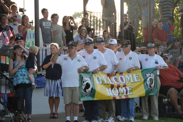 Vietnam Veterans from the Liberty County Chapter 789, render honors during the singing of the national anthem while holding a banner welcoming home 293rd Military Police Company, 385th MP Battalion, 3rd Infantry Divsion upon their arrival home to Fort Stewart, Ga., from their year-long deployment in Afghanistan, July 21.