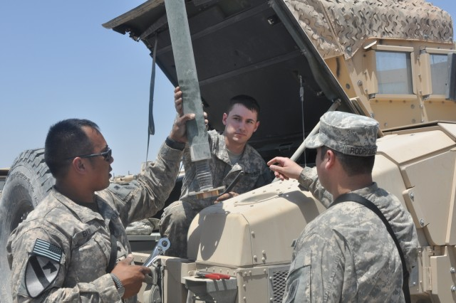 Specialists Phuc Bui and Bryan Primeaux and Sgt. Marcos Rodriguez, all mechanics with 2/156 Infantry Battalion, 3rd Sustainment Brigade, 103rd Sustainment Command (Expeditionary), remove the last antenna from a High Mobility Multi-Wheeled Vehicle before turning it in to the Redistribution Property Accountability Team.