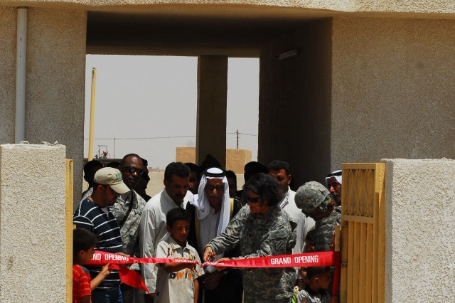 Local villagers and children from the Albu Hamaad village and surrounding area gather for the grand opening of the Al Haneen primary school held in Albu Hamaad, July 19.  Eighth grader Mohammad Fahad holds the tape next to Village Sheik Dawood Salman Rabia as Lt. Col. Nora Marcos, commander for DSTB, 3rd ID cuts the ribbon.