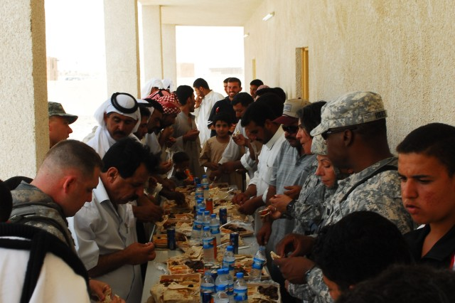 Local villagers, Soldiers and children gather for refreshments following the grand opening ceremony for the Al Haneen primary school held in the village of Albu Hamaad,  July 19.
