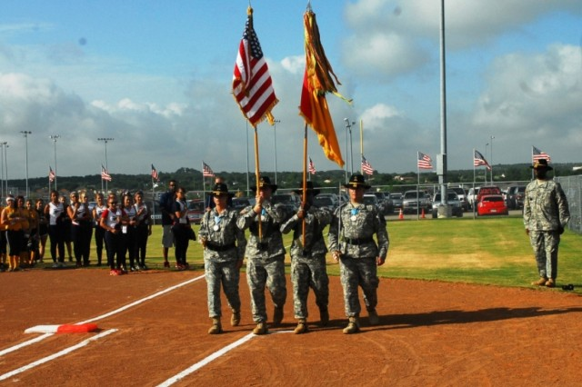 FORT HOOD, Texas-The 2nd Brigade Combat Team, 1st Cavalry Division\'s Sergeant Audie Murphy Color Guard march to home plate during the opening ceremony for the 2010 Amateur Softball Association's 14 and under B-Girls Fast Pitch Southern National Tournament, at the Lions Club Park in Killeen, Texas, July 29. The color guard is led by Sgt. 1st Class Mark Haliburton (right).