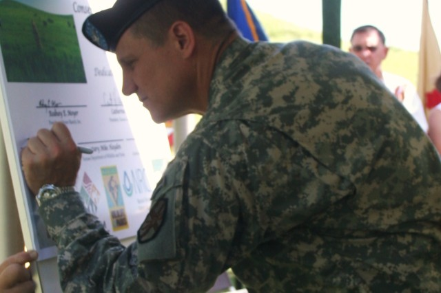 Col. Kevin Brown, Fort Riley garrison commander, signs a conservation easement July 22, protecting Moyer Ranch near Fort Riley, Kan., from future development. The easement is an agreement between the Kansas Land Trust, Fort Riley's Army Compatible Use Buffer Program, Natural Resources and Conservation Service, Farm and Ranchland Protection Program and the Kansas Department of Wildlife and Parks.