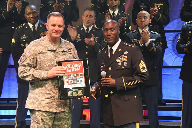 FORT SAM HOUSTON, Texas - Maj. Gen. Perry Wiggins, the deputy commanding general for U.S. Army North and Fort Sam Houston, is presented a Soldier Show plaque by Sgt. 1st Class Earnest Baskin, the show's noncommissioned officer in charge, following the 2010 U.S. Army Soldier Show July 27 at Trinity University's Laurie Auditorium in San Antonio. Wiggins served as the host and guest speaker for the event. Following the performance, he presented a plaque to the show's cadre and a coin for excellence to each performer.