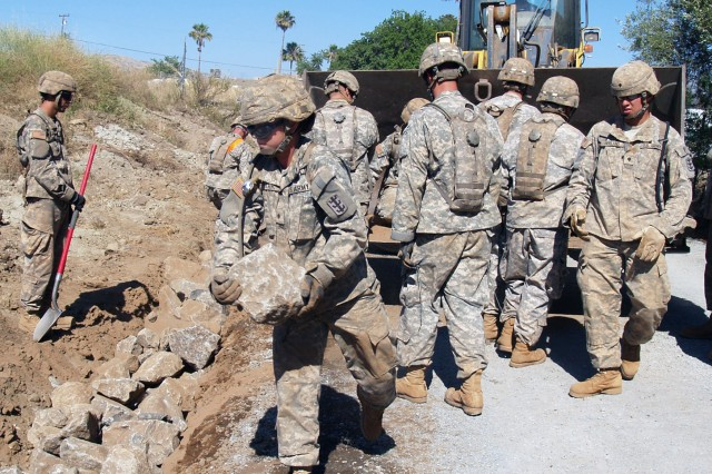 FORT BLISS, Texas - Spc. Heather Clark, 82nd Engineer Support Company, 65th Engineer Battalion, carries a large stone to a newly constructed ditch.  The stones are placed in the ditch to help control the flow of water and to help prevent soil erosion.