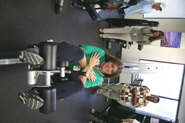 Phylissa Shannon, Morale, Welfare and Recreation sports specialist, demonstrates how to properly do a situp to U.S. Army Space and Missile Defense Command/Army Forces Strategic Command employees during a Fitness Life Improvement Program equipment orientation July 28.