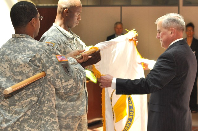 "FORT MCPHERSON, Ga. (July 29, 2010)--U.S. Army Forces Command (FORSCOM) Assistant Deputy Chief of Staff, G-6 William ""Bill"" T. Lasher is presented the Senior Executive Service (SES) flag by Master Sgt. Korey Carter. FORSCOM G-6 Sgt. Maj. Fabian Bradshaw assists Lasher in unfurling the SES flag during an appointment ceremony Thursday, at FORSCOM Headquarters. The SES flag was designed to provide increased visibility to SES members and recognize them as leaders along with General Officers of the United States Army.  The flag was approved 1 May 1998 as a positional flag.  The designation band on the keystone is patterned from the Army emblem and identifies the member as part of the United States Army.  The white background was selected as it is the primary color used by the Army for positional flags.  Dark blue is the color used on the Presidential Flag."