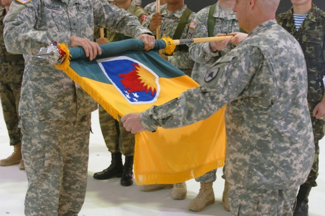 Brig. Gen. Al Dohrmann (left), Bismarck, N.D., outgoing commander of Multinational Battle Group East, and Command Sgt. Maj. Jack W. Cripe, Bismarck, N.D., outgoing command sergeant major for MNBG E, roll up the 141st Maneuver Enhancement Brigade flag during a Transfer of Authority Ceremony at Camp Bondsteel, July 24. Brig. Gen. Dohrmann officially handed over command of MNBG E to Col. Francisco J. Neuman, Ponce, Puerto Rico, during the ceremony. (U.S. Army photo by Sgt. Jerry Boffen, 130th PAD)