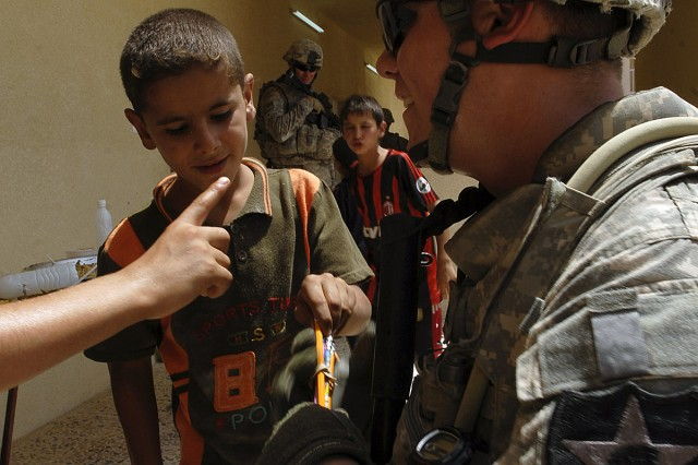 TAJI, Iraq - Sgt. Charles Snyder, a squad leader with 4th Stryker Brigade Combat Team, 2nd Infantry Division, hands out pencils to Iraqi children counting in English inside a newly opened school in Malahma July 24. Insurgents blew up the school in 2007 days before it opened, but 2nd Battalion, 23rd Infantry Regiment Soldiers, Iraqi Security Forces, and the Government of Iraq helped refurbish and reopen the school so local children would have a closer school to attend. Snyder, a Grandview, Wash., native handed out pencils and helped provide security alongside ISF and 2nd Bn., 23rd Inf. Regt., Soldiers.