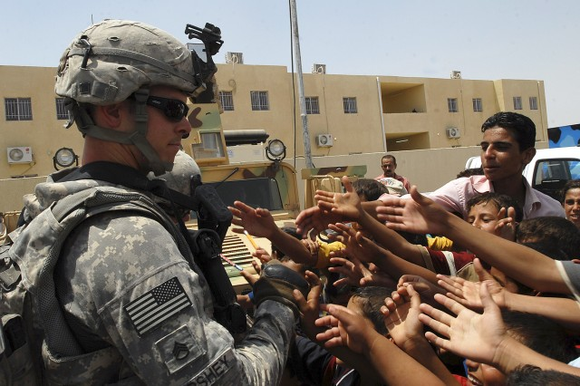 TAJI, Iraq - Staff Sgt. Benjamin Forshey, a platoon sergeant with 4th Stryker Brigade Combat Team, 2nd Infantry Division, holds a pencil as a mass of hands spring toward him during a school opening in Malahma July 24. Local children no longer have to walk nearly 10 kilometers to get to school because of the efforts of 2nd Battalion, 23rd Infantry Regiment, Iraqi Security Forces and local contractors.