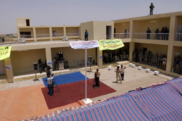 TAJI, Iraq - Iraqi media set up cameras while Iraqi Security Forces provide rooftop security during the opening of a school in Malahma July 24. The school, which was blown up by insurgents at the height of the Surge, opened without any incidents with the  help of 2nd Battalion, 23rd Infantry Regiment, 4th Stryker Brigade Combat Team, 2nd Infantry Division, Iraqi Security Forces, and the Government of Iraq.