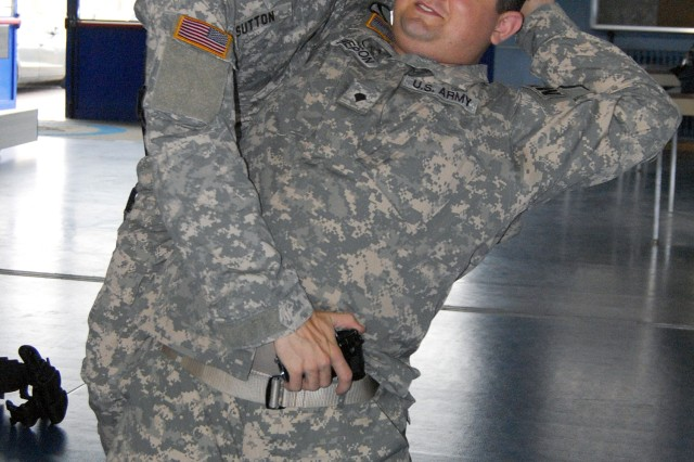 Sgt. Jeremiah D. Sutton (standing)demonstrates the proper technique for disarming a gunman with Spc. Bradley Emerson during Active Shooter training.