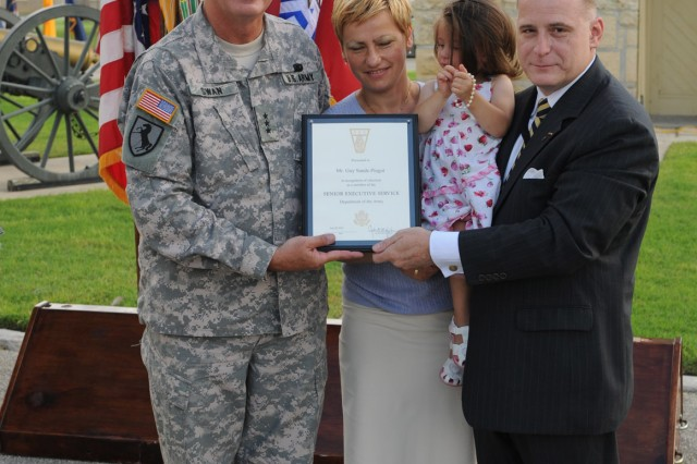 FORT SAM HOUSTON, Texas - Lt. Gen. Guy Swan III, commanding general, U.S. Army North and Fort Sam Houston, presents a certificate to Guy Sands-Pingot after swearing him in as a member of the Senior Executive Service as U.S. Army North welcomed its new deputy to the commanding general during a ceremony in the historic Quadrangle July 30 as his wife, Valentina, and daughter, Maria, watch on. Sands, who is a brigadier general in the Army Reserve, is the first member of the Senior Executive Service - the uppermost ranks of federal civil service - to serve in the position at Army North