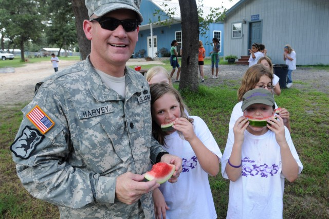 FORT SAM HOUSTON, Texas - Lt. Col. Mike Harvey, chief, air operations cell, Army North, takes a watermelon break with his daughter, Mattie, and her fellow campers July 29 at Operation Purple, a camp for children of deployed parents, hosted by Blue Streak Stables Horsemanship Camps in Seguin. Harvey, along with fellow Soldiers from Army North, took a day to talk about the military and to lead 55 young girls through leadership challenges and relay races.
