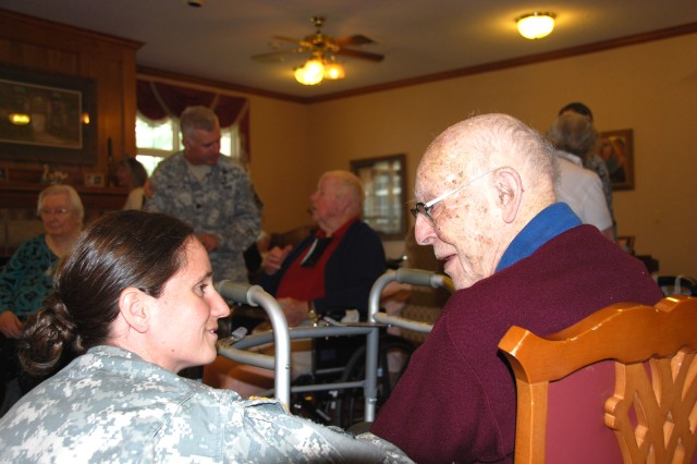 Maj. Nikki Blystone, a planning officer with First Army G-4, talks with Laird Addis, age 96, during a stop at the Bickford Cottage Assisted Living Center in Iowa City, Iowa, on July 23. Blystone and six other First Army representatives met with veterans and other retirees at the center the day before participating in the 2010 Bix 7 Race in Davenport, Iowa.