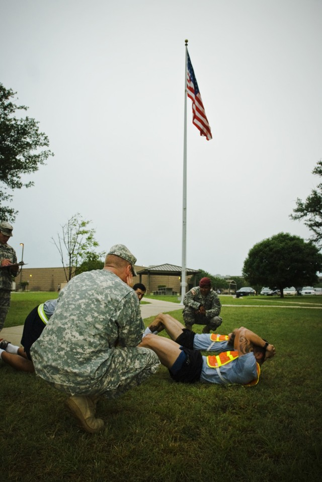 FORT HOOD, Texas- Candidates perform sit-ups underneath the watchful eye of Long Range Surveillance (Airborne) unit members, July 27, on West Fort Hood, Texas.  These Soldiers must complete a gauntlet of Ranger led physical training events to be cons...