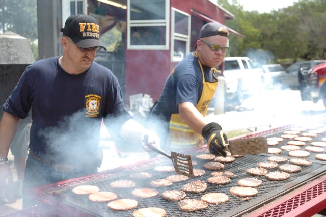 Fort Hood Soldier and Gatesville volunteer fireman Staff Sgt. Ronald Robbins, assisted by fellow firefighter Jeffrey Sanders, flips burgers for the July 28 Warrior Transition Brigade's Organizational Day at Belton Lake Outdoor Recreation Area (BLORA). Robbins is the activities coordinator for the 1st Battalion, WTB. Sanders, along with Gatesville fire chief Billy Vaden, spent their day off grilling more than 700 hot dogs and hamburgers for the hungry warriors and their families as a way to give back to the Soldiers for all they do. The USO and American Red Cross donated the grub, with leftovers given to the Killeen homeless shelter. (Photo by Gloria Montgomery, WTB Public Affairs)
