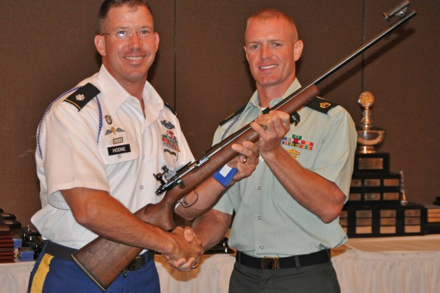 MARINE CORPS BASE QUANTICO -- Staff Sgt. Brandon Green, U.S. Army Marksmanship Unit, is presented a Trophy Rifle by Lt. Col. Daniel Hodne, commander, USAMU, after winning the individual championship at the 49th Interservice Rifle Championship. Green won six individual titles and was a member of three first-place teams. (Photo by Michael Molinaro, USAMU PAO)