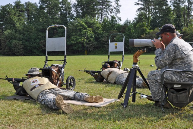 MARINE CORPS BASE QUANTICO -- Team Coach Sgt. 1st Class Emil Praslick, U.S. Army Marksmanship Unit, shouts instructions to Sgt. 1st Class Grant Singley (left) and Staff Sgt. Joel Micholick (right) as they shoot from 600-yards prone during the 10-man Interservice team championship match July 27. The USAMU Service Rifle team won the match and swept every major award at the championships. (Photo by Michael Molinaro, USAMU PAO)