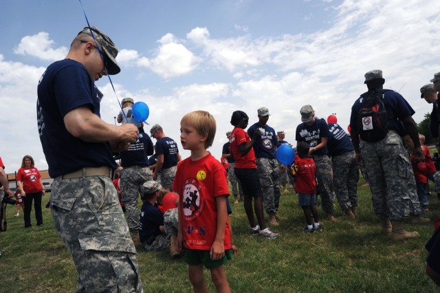 "Towards the end of 2010 TAPS Fort Hood Military Survivor Seminar and Good Grief Camp, the surviving children of the fallen had a chance to release a balloon with a private message. Here, Soldier/Mentor David Riecke helps Wayne secure his message. ""I miss you,"" Wayne said."