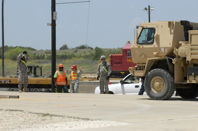 FORT HOOD, Texas- Sgt. Ryan Boyd (far left), an infantryman assigned to 2nd Battalion, 7th Cavalry Regiment, 4th Brigade Combat Team, 1st Cavalry Division, guides a light medium tactical vehicle during rail head operations, here, July 29.