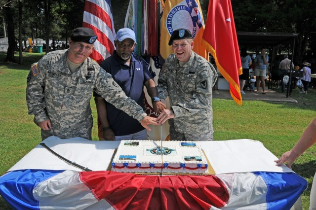 (L to R) Sgt. Maj. William Kaundart, senior enlisted leader to the commanding general; Al Thomas, acting deputy to the commanding general; and Brig. Gen. Christopher Tucker, USASAC commander; cut the ceremonial cake during USASAC\'s 45th anniversary festivities.