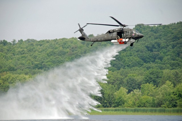 A UH-60 Blackhawk helicopter of the New York Army National Guard's 3rd Battalion 142nd Aviation in Latham conducts a training run with the Firehawk fire fighting system over the Mohawk River on August 4.  The unit practices water bucket and Firehawk operations annually in case they are need to support the civil authorities with fighting wild fires.   The Firehawk allows the air crew to siphon 1000 gallons of water in about one minute and deliver it to the scene of a fire. The crew can control the rate of release based on the firefighters needs.