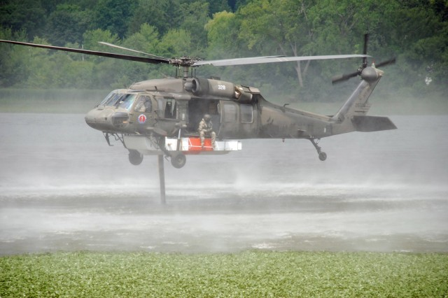 A UH-60 Blackhawk helicopter of the New York Army National Guard\'s 3rd Battalion 142nd Aviation in Latham hovers above the Mohawk River as the crew fills the Firehawk firefighting system attached to the underside of the helicopter.  A pump and hose system allows crews to refill the Firehawk tank in flight.The unit practices water bucket and Firehawk operations annually in case they are need to support the civil authorities with fighting wild fires.  The Firehawk allows the air crew to siphon 1000 gallons of water in about one minute and deliver it to the scene of a fire. The crew can control the rate of release based on the firefighters needs.