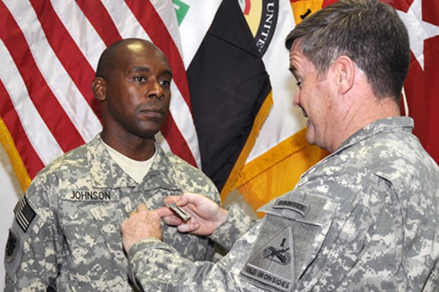 BAGHDAD - Maj. Gen. Terry A. Wolff, United States Division-Center commanding general, places the highest warrant rank on Chief Warrant Officer 5 Randy Johnson during his promotion ceremony in the USD-C division conference room Aug. 4. Johnson joined the U.S. Army March 16, 1984, and became a warrant officer in March 1994. He has served proudly for 26 years and says he will continue to do so at the pinnacle of his career for several more.   (U.S. Army photo by Spc. Kim Wilkins, 1st Armd. Div., USD-C)