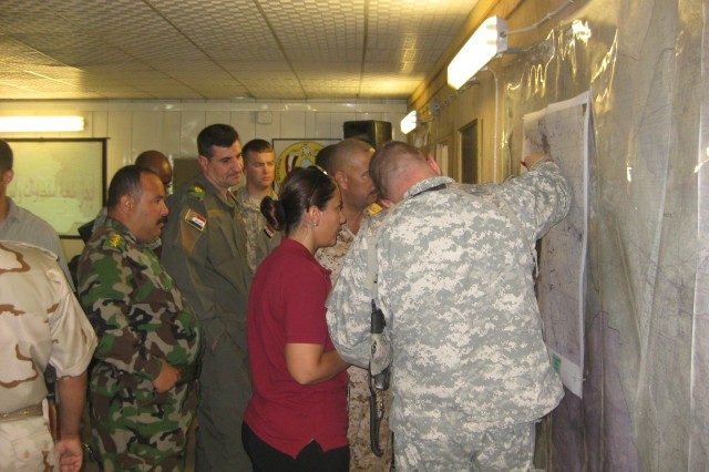 Leaders of the 3rd Heavy Brigade Combat Team, 3rd Infantry Division and the 8th Iraqi Army Division indicate areas of interest and surveillance on a map during a meeting July 18 at Contingency Operating Site Kalsu.