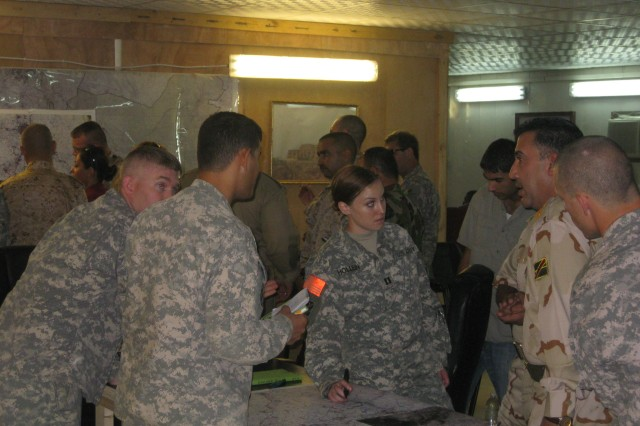 Capt. Joan Hollein,  assistant intelligence officer for the 3rd Heavy Brigade Combat Team, 3rd Infantry Division, verifies the Sha'baniyah intelligence collection plans with 30th Iraq Army Brigade intelligence officer, Lt. Col. Khalid, July 18 at Contingency Operating Site Kalsu.