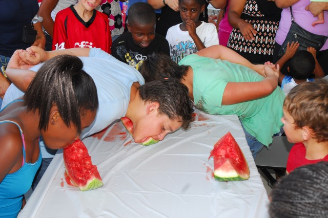 A group of children battle it out during a watermelon eating contest at Tuesday's National Night Out event. Quest Benevento won the event.