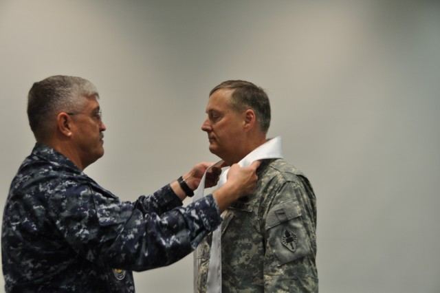 Navy Chaplain (Capt.) Michael Langston places the stole around Chaplain (Col.) David Smartt's neck during a ceremony Monday to signify Smartt's transition as director of the Armed Forces Chaplaincy Center. Smartt takes over for Air Force Chaplain (Col.) Steven Keith.